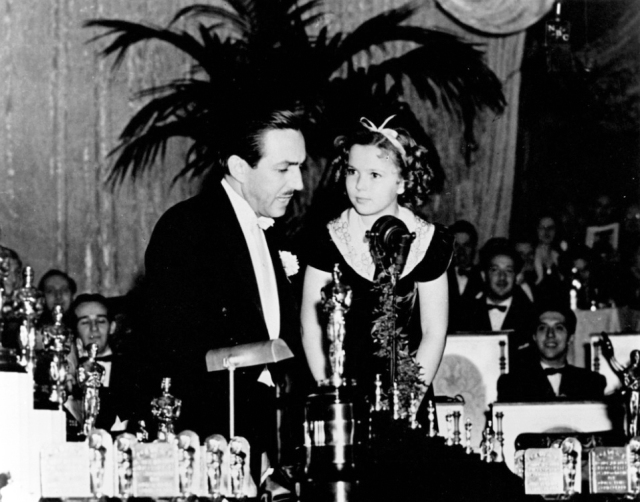 Temple presenting Disney with his Oscar.